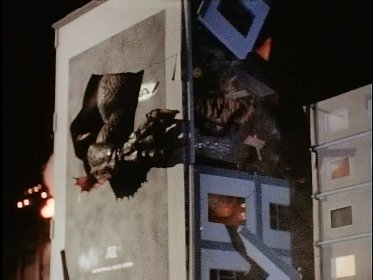 Kraa punches through a 1998-ubiquitous Godzilla advertisement.