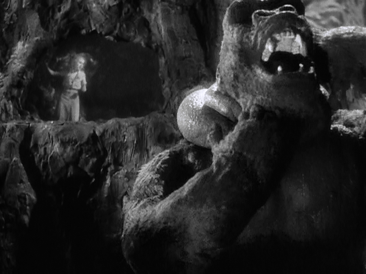 Kong is torn between grabbing Jack Driscoll and saving Ann Darrow.